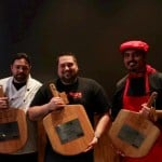 three members from 786 degrees standing and holding their pizza pans which are engraved with special lettering as a trophy for their win at the Pizza Competition